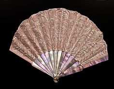Fan  Duvelleroy  (French, founded 1827)  Date: ca. 1910 Culture: French Medium: mother-of-pearl, silk, metal Dimensions: 8 3/4 in. (22.2 cm) Credit Line: Brooklyn Museum Costume Collection at The Metropolitan Museum of Art,