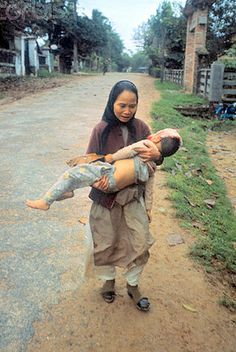 11 Feb 1968, Hue, South Vietnam --- South Vietnamese Woman Carrying Her Wounded Son