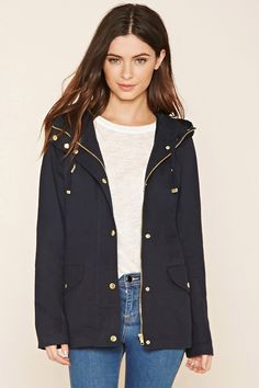 A woven parka featuring a drawstring hood, zippered and buttoned front, long sleeves, a hidden drawstring waist, zippered chest pockets, button-flap pockets near the waist, and buttoned shoulder tabs.