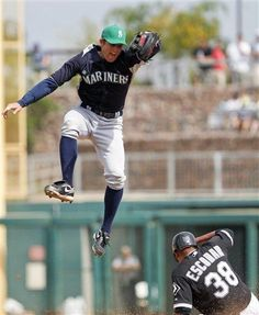 Seattle Mariners shortstop Brad Miller, left, jumps for a wild throw