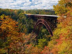 Autumn Reflections  New River Gorge Bridge. by BuiterPhotography.com  Soft clouds and autumn colors frame the New River Gorge Bridge on a mid-October day.   The steel arch span is 1700 feet long and for many years was the longest in the world.  The highway crosses the New River 876 feet below.  This image taken on Friday just before the Annual Bridge Day celebration.   Eight stops of light reduction were used to create a 3 second daytime exposure to blur away the active highway traffic.