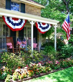 This home has beautiful tropical foliage landscaping with a front porch outfitted for 4th of July celebrations!