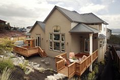 Suburbia home exterior with a cedar deck, a hillside backyard and plenty of land to improve their landscaping. Click on the pin to see the difference between a brick patio and wood deck. #wooddeck #backyard