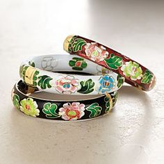 """Cloisonné was developed thousands of years ago during the Byzantine era and traveled via the Silk Road to China, where it has flourished as an art form ever since. To create a design in cloisonné, an artist's original sketch must be traced using thin strips of wire. Into this wire """"scaffolding"""" is inserted powdered enamel that, when baked, fills the outlines and creates a porcelain-like appearance. These hinged bangles feature stylized peonies.  $25.00 per bangle."""