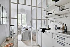 Bedroom with glass wall to the white kitchen
