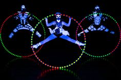 Three performers with three Cyr Wheels in black light show Crystal Light- Anta Agni.