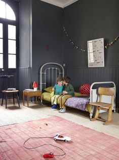 Dark grey walls, pink rug and yellow bedding in children's room of the home of French photographer and stylist Aurélie Lécuyer. Photography: Melanie Rodriguez.