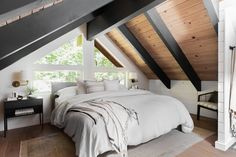 The large windows and predominantly white color scheme allow the use of wood slats and dark beams on the ceiling without giving a closed-in feel to the attic bedroom. DDCO Cabin Main Bedroom and Ensuite Bath | ORC Reveal Source by diybystyle The post DDCO Cabin Main Bedroom and Ensuite Bath | ORC Reveal appeared first on Susannah Kenny Interiors. Bedroom With Bath, Bedroom Retreat, Cozy Bedroom, Attic Bedroom Designs, Ceiling Treatments, Attic Remodel, Wood Slats, Large Windows, Upholstered Chairs