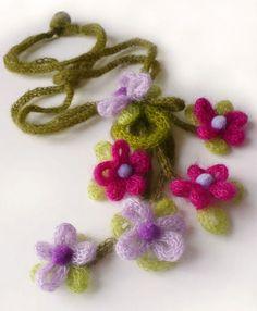 Collana con lavorazione a tubolare realizzata con il tricotin mecanique.      Il centrale di ciascun fiore è una perla di feltro.