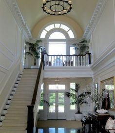 Isn't this two story foyer just stunning?  The wainscoting and crown moldings add such class and style. The floor to ceiling window brightens and is a beautiful focal point.
