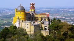 The Pena Palace in Sintra, Portugal is one of the Straight Out of Disney: Visit 12 of Europe's Fairytale Castles  according to Travioor | 24/10/2016 A registered UNESCO world heritage site, it is visible from Lisbon, thanks to its breath-taking location at the top of the Sintra Mountains.  #Portugal