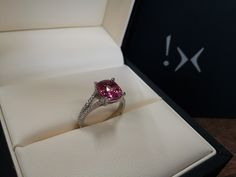 3.31 carat cushion cut padparadscha sapphire    0.41 carats round cut side diamonds    18K white gold