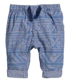 Pants in woven organic cotton fabric with a printed pattern. Elasticized waistband with decorative drawstring, and sewn cuffs at hems.