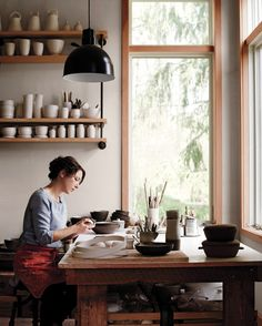 "Cain took up ceramics three years ago when she ""wanted to do something on her own that was physical, not computer-based."" Her table, built on reclaimed-wood beams, rests on casters, so it moves easily around her workshop. An elegant porcelain-enamel lamp (from Barn Light Electric) hangs overhead."