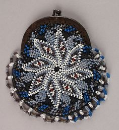 Date Made: c. 1900  Description:  Coin or change purse; beaded opalescent blue, white, and red starflower motif on a black crocheted ground, beaded looped fringe. Starflower motif in opalescent blue outlined in white with red accents. Edge of coin purse is accented in diagonal beaded bands of opal, royal blue, and brown. One side of the looped fringe in white, opal, and brown; other side in white, opal, and royal. Metal frame and clasp. Lined in navy blue silk.