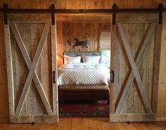 We love this gorgeous rustic bedroom. The Bi-parting barn doors add an extra rustic authenticity to the room. Via: Susan Dahlin Bashford