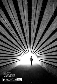 Central Park Tunnel, by Christopher Utano - Photo was taken in Central Park NYC. I noticed the strong lines in the bricks overhead and seen potential for a good black and white composition. I switched to my 10-20mm lens to get as much of the lines in the shot as possible. I waited for someone to approach the tunnel from the other side to give the photo added depth and lead the eyes to a subject.