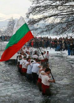 Bulgarian men from Kalòfer doing the traditional 'Horo' dance in the icy waters of the river Tundzha for the Epiphany Day celebrations. Kalòfer is a town in central Bulgaria.