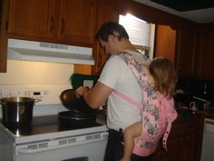 Real men - Wearing toddler in pink carrier AND cooking.  So hot!