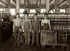"""November 1908. Cotton mill workers at Daniel Manufacturing Co. in Lincolnton, North Carolina. Four doffers. Boy on left end (knee pants) said he had worked in the mills for seven years and some nights. At nights they work 12 hours, without any hour off for lunch. Eat when they can. Some of them """"eat a-workin'."""" Photograph and caption by Lewis Wickes Hine"""