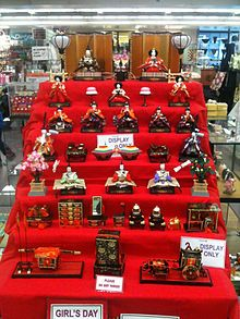 Hina-matsuri (Japanese Doll Festival).  Platforms covered with a red carpet are used to display a set of ornamental dolls  representing the Emperor, Empress, attendants, and musicians in traditional court dress of the Heian period.