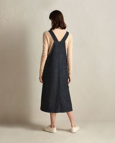 Straight-cut apron dress in a medium-weight, supple, indigo-dyed, stretch denim. Two carpenter patch pockets. Pinafore-style back. Back patch pocket. Two corozo shank buttons at either side. Twin needle topstitching.