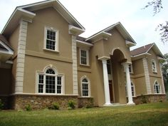 architectural house design with artistic gate and two story and white molding window and green landscape and with the most popular exterior house color of cream