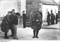 French resistance fighters being arrested by German troops, France, Jul 1944. Note the camouflage smock worn by the Germans. Toward the end of the war, German infantry troops were adopting the smock first worn by the Waffen SS,