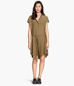 Short-sleeved shirt dress in woven crêpe fabric with a tie belt at waist and buttons at front. Unlined.