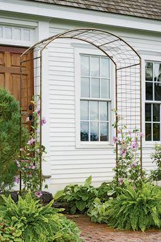 Ejemplo  de pergola realizada en  madera e hierro para hacer guiar plantas trepadoras de flores .