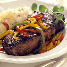 A rainbow of sweet peppers tops juicy, inch-thick pepper-coated steaks in this dinner recipe.