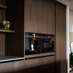 De moderne, donkere keuken van de hand van Meubelmakerij Den Berg heeft zijn allure te danken aan de combinatie van materialen en functies. In het grijze kookeiland is een bar en een boekenkast verwerkt waardoor de woonkeuken naadloos overloopt in de woonkamer #donkerekeukenideeën #modernekeuken #grijskookeiland #woonkeuken #woonkeukenmetbar #meubelmakerijdenberg #meesterlijkmaatwerk Divider, Kitchen Cabinets, Modern, Room, House, Furniture, Home Decor, Give Thanks, Bedroom