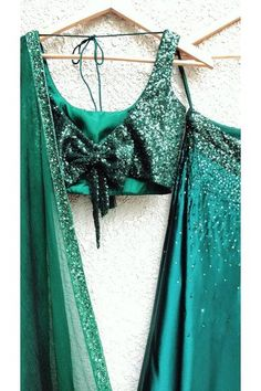 Emerald green sequins blouse with bow back, satin skirt and 2 tone pure chiffon dupatta with handwork border The Blouse is fully embellished by hand with sequins Remember to see the hot bow at the backCan be customised in any colour of your cho. Lengha Blouse Designs, Fancy Blouse Designs, Bridal Blouse Designs, Blouse Neck Designs, Blouse Patterns, Blouse Styles, Stylish Blouse Design, Indian Designer Outfits, Lehnga Dress