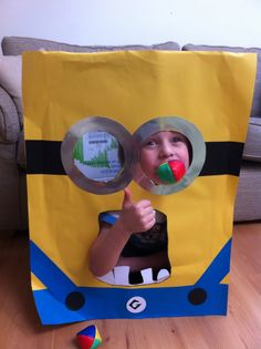 Minion party throwing ball game made with ideas from Pinterest! Used old big cardboard box I had, cut out eyes & mouth holes. My son helped make with me, I cut out circle shapes and he stuck on.  He also drew the teeth & I cut out.  I think More fun was had climbing in it!