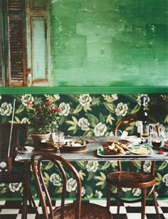 The beauty of age: big mirror, vintage wallpaper, old green walls, old French shutters and Thonet bistro chairs.