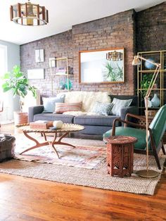 brick wall + light wood floors + gray couch with bright green pop + symmetry in shelves + light + rugs + decor