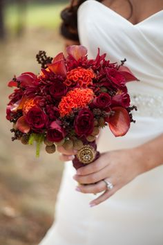 This Fall wedding bouquet was designed with orange celosia, red spray roses, red calla lilies and a variety of seasonal items.