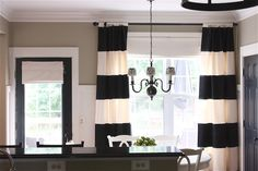 Love the striped curtains, black door, and board and batton mouldings in the breakfast area.
