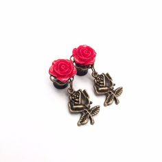 This is a pre made pair of ear plugs featuring a red rose in the centre of a bronze plate with a bronze rose charm hanging underneath. The plate is attached to the front of 8mm (0g) acrylic flared ear plugs. *Please note we do not take responsibility for blow outs. Please take into consideration the size and weight when purchasing ear stretchers. We only exchange/refund ear stretchers/plugs that are damaged or incorrectly sent, we do not refund or exchange on blow outs.By pu...