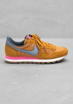 NIKE These sneakers have a vintage running shoe look, combining both a suede and textile upper.