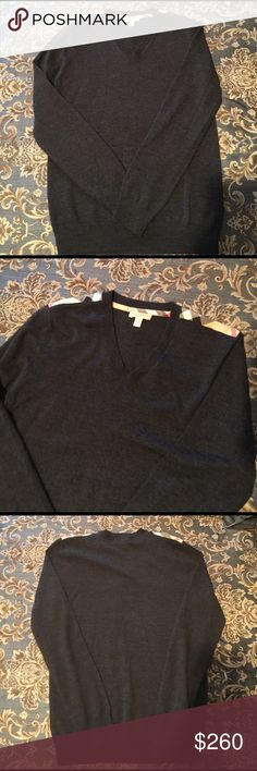 Burberry sweater Dark charcoal grey merino wool v neck with Burberry check pattern in shoulders, ribbed waist band. Looks good alone or can wear tee or button down underneath. Beautiful-worn ONE time!! Perfect! Burberry Sweaters V-Neck