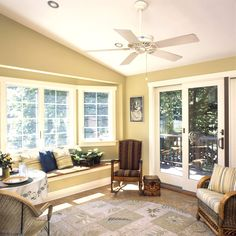 Comfy Sunroom Interior Nuance with Gold Wall Paint Color and Excellent Bay Window and Classic Wood Rocking Chair also Rattan Chairs and Round Floral Area Rug and Rustic Floor Tile and White Ceiling Fan