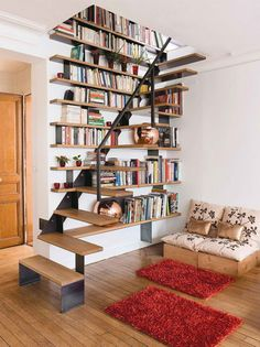Love how minimalist this is while still being warm and functional. The two red rugs, the copper ball on bookshelf, the floating stairs....