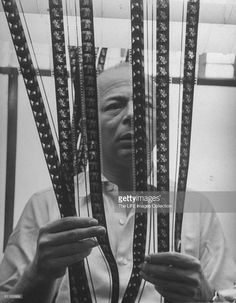 """""""Movie director Billy Wilder standing behind strips of film in cutting room while he decides which should go into finished movie."""" Photo by Bob Landry. Image retrieved from Getty Images."""