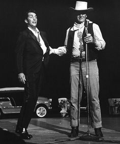 """HOLLYWOOD COWBOYS - Dean Martin & John Wayne on stage for a benefit show.  Wayne & Martin appeared in two Western films together--""""Rio Bravo"""" and """"The Sons of Katie Elder"""" - Publicity Photo."""