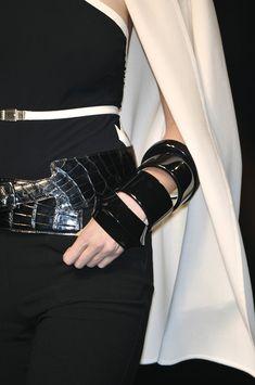 Hermès. Crocodile belt and black resin bangles.