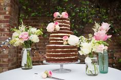 Naked Chocolate Cake on cake stand with pink & white stemmed flowers in jars - Image by Lily & Frank Photography - Lace Claire Pettibone Gown & Jimmy Choo Shoes for a Bright Pink & Turquoise Wedding with Grey Groomsmen & Chocolate Naked Cake.
