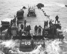 """""""Rhino"""" ferry RHF-12 pendant les premiers jours, 6-9 Juin 1944. Le RHF-12 était sous le commandement de Carp. J. D. Lamont, CCE, USNR et Ens. H. E. Cobb, CCE, USNR. Note: """"SeaBee"""" insigne présent sur la lame de bulldozer et sur les """"Rhino"""""""