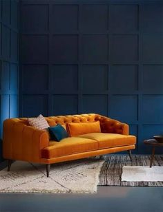 mustard yellow velours couch in a dark blue room