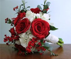 Red and white bouquet of roses, hydrangea, gypsophila, and berries. Wrapped with satin and lace, accented with pearls.